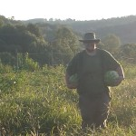 chris with watermelons in field farm